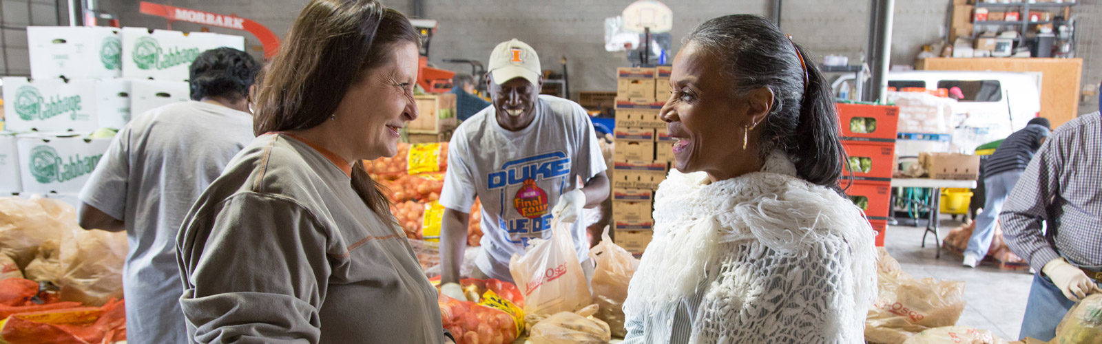 Women smile at food pantry