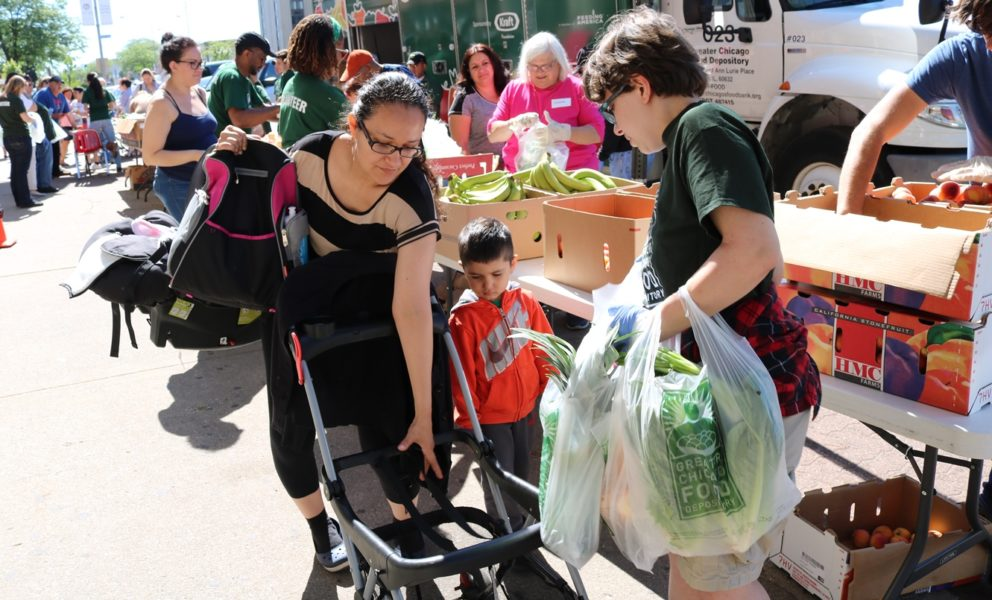 Maricela receives bags of produce from a FRESH Truck volunteer