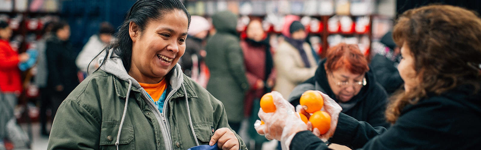 A woman receives oranges at a food program