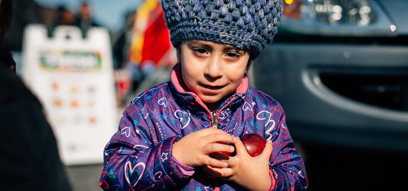 A child holding apples at a FRESH Truck