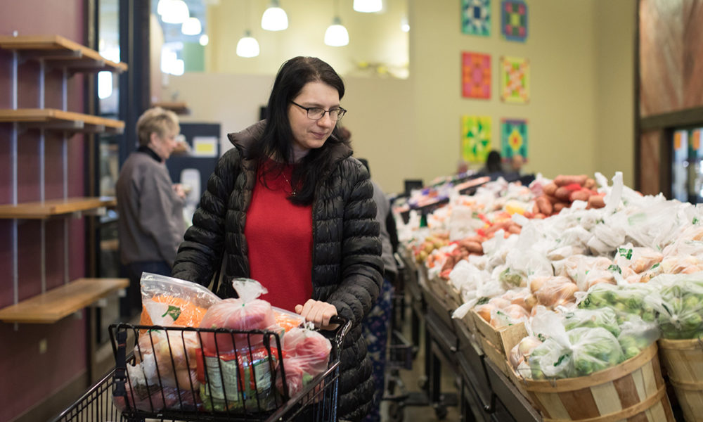 Person with shopping cart selects produce at Willow Creek Food Pantry