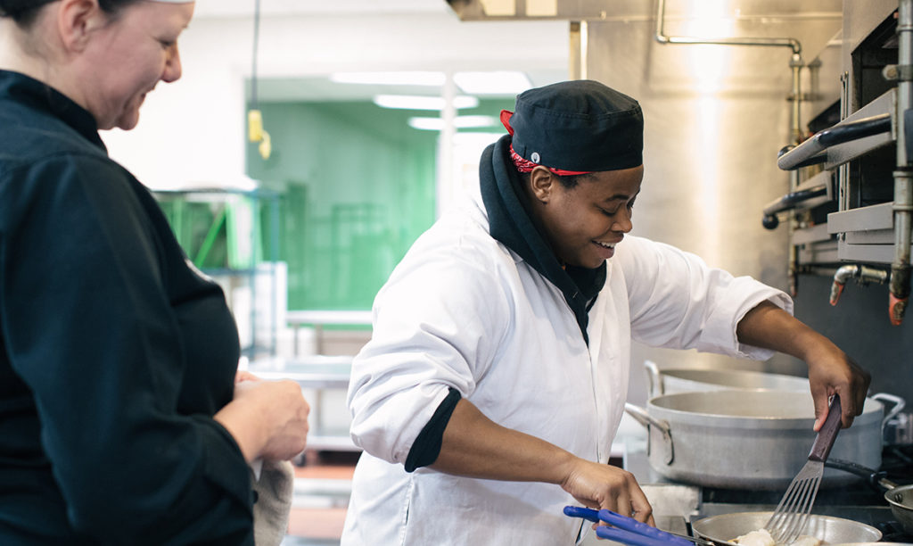 Chef Emily observes a student cooking in Chicago's Community Kitchens