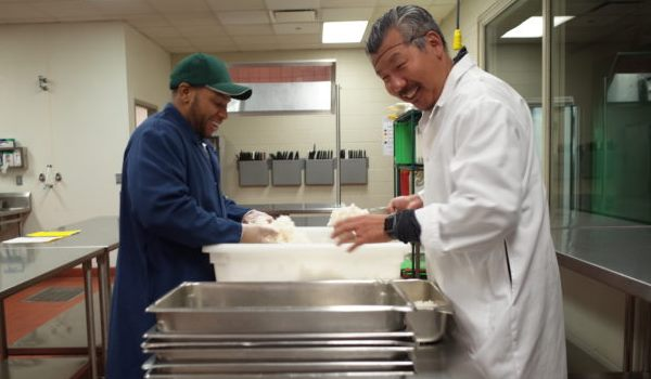 A Chicago's Community Kitchens student prepares food with Chef Bill Kim