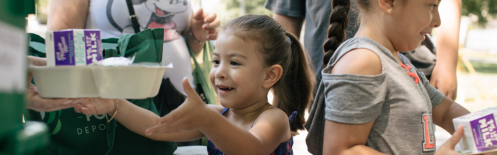 Children receive meals from the Food Depository's Lunch Bus