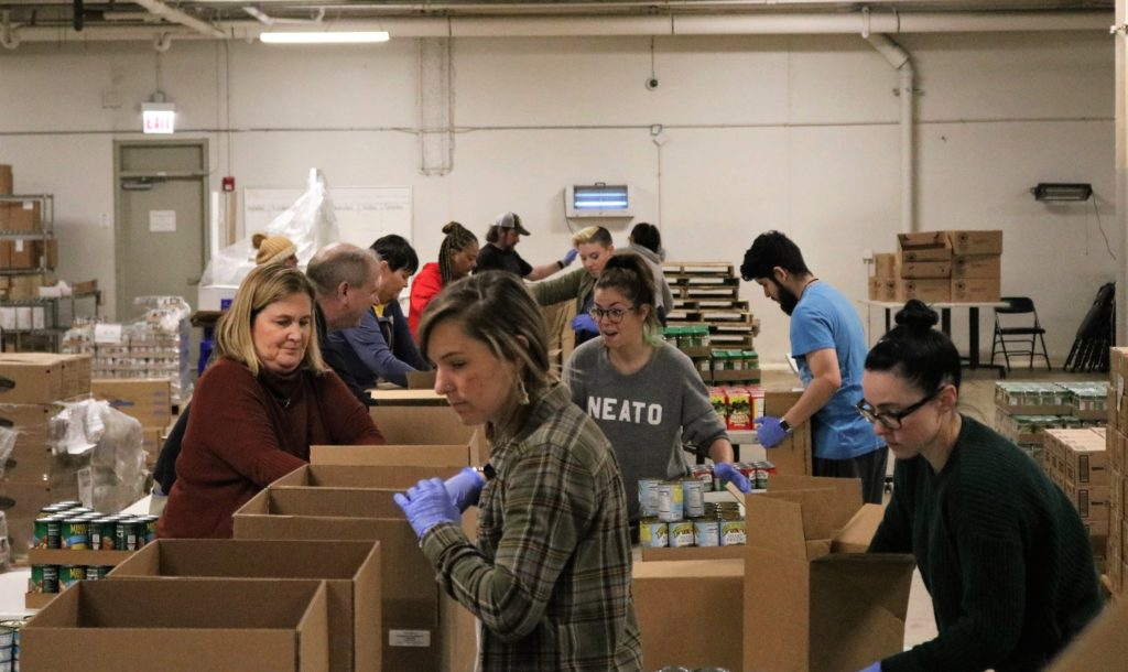 Volunteers pack boxes of shelf-stable food in the Greater Chicago Food Depository warehouse