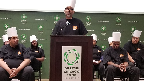 Demetrius Newman addresses the audience during the Chicago's Community Kitchens graduation.