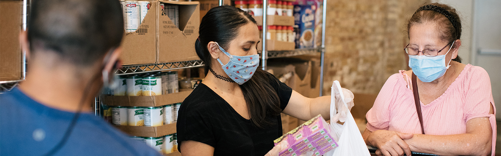 People wearing masks fill bags with food