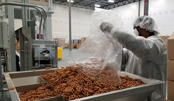 A CREDMADE worker loads a large batch of pretzels into the packing machine.